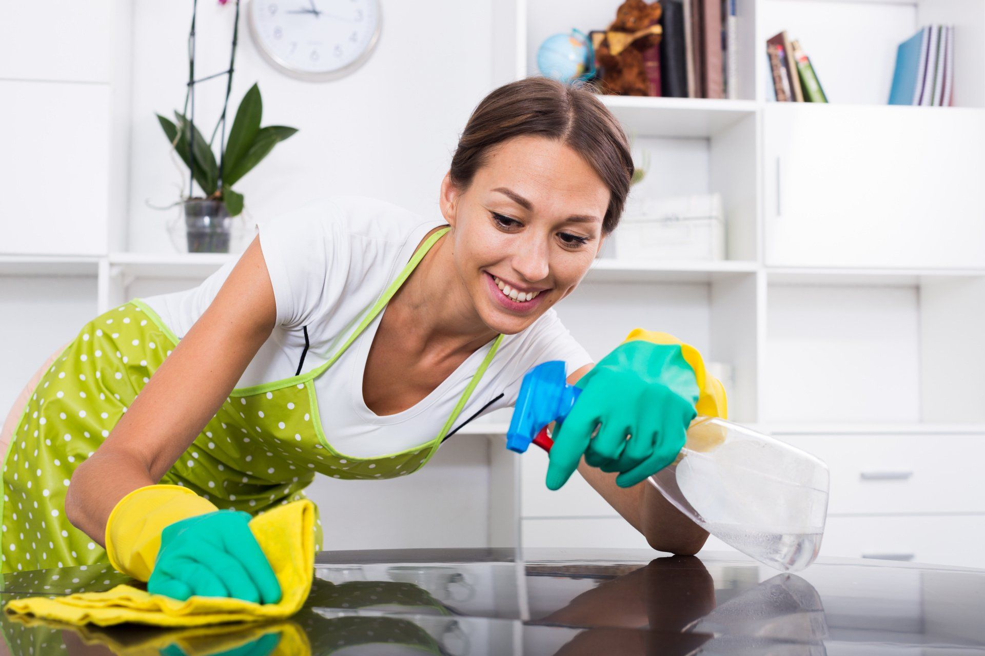 a woman in apron and rubber gloves cleaning a kitchen counter