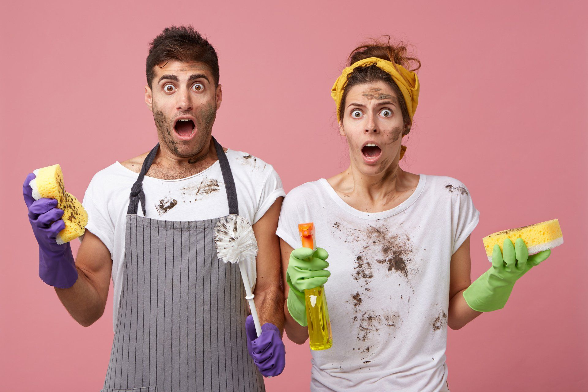 man and woman covered in dirt holding cleaning supplies