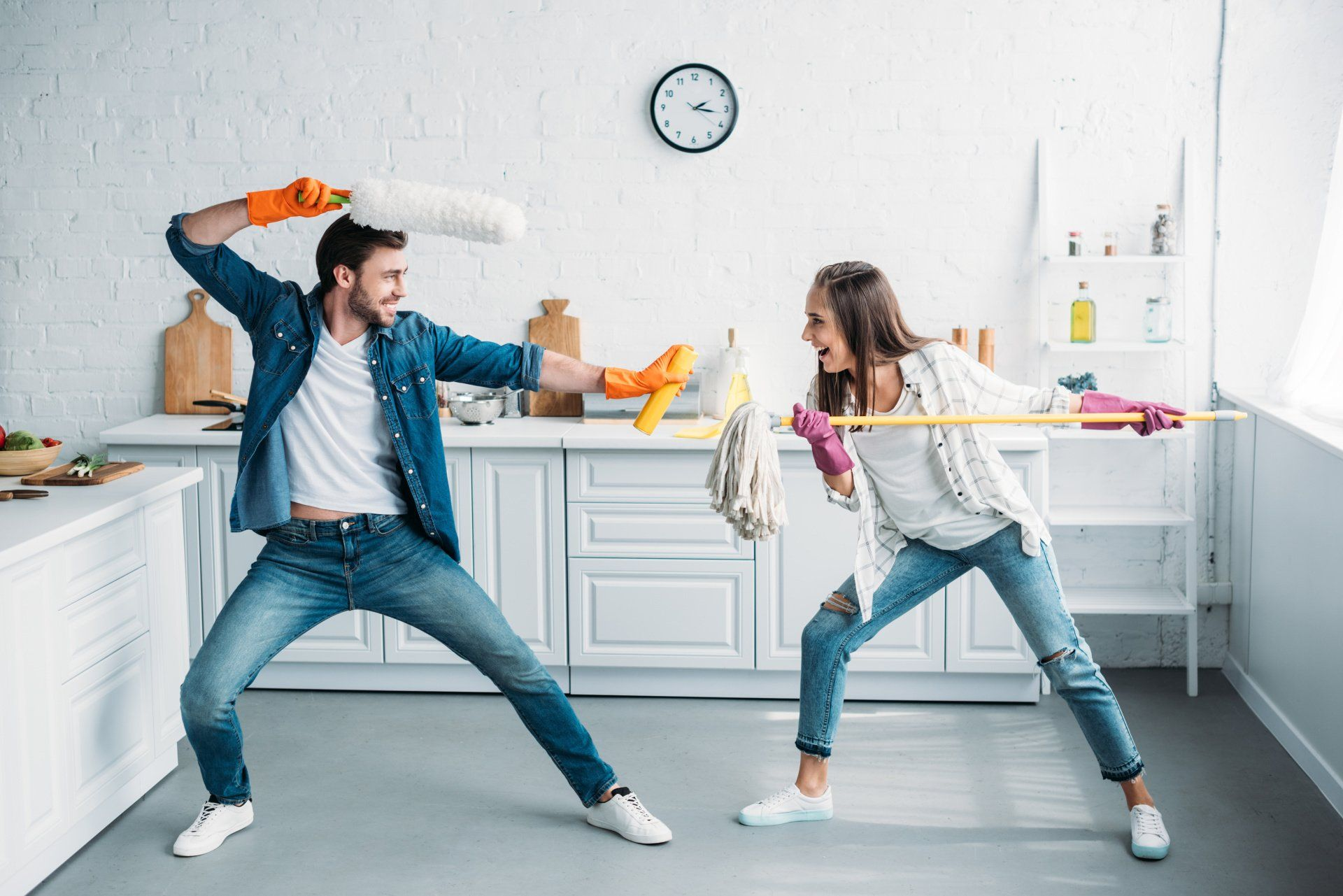 man and woman playfully fighting with cleaning products