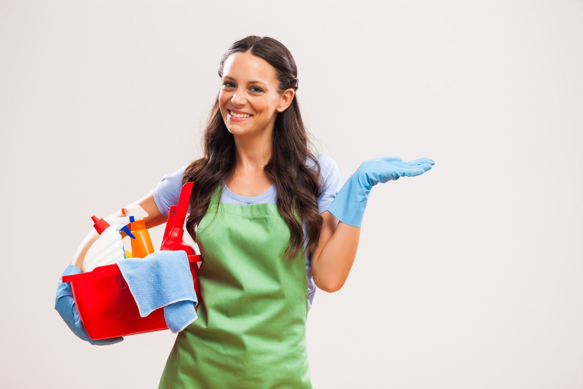 a cleaning service worker smiling and holding cleaning supplies