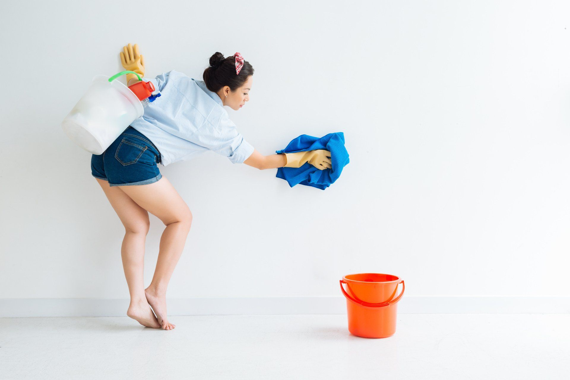 woman cleaning walls with a blue towel