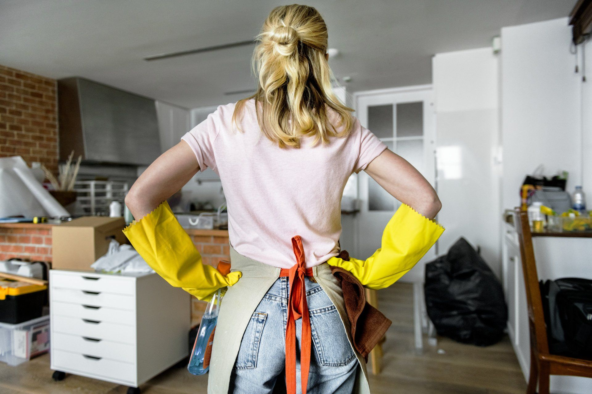 a woman looking at a huge mess in the kitchen to clean up