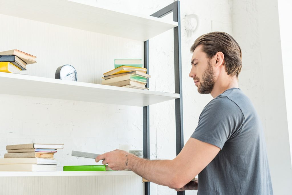A young man with facial hair puttign a book back on a shelf to tidy up a living room for guests.