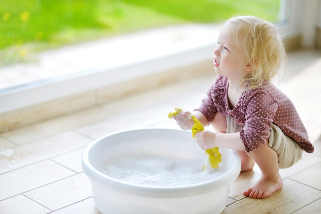 A small blonde toddler using a cleaning bucket and gettign ready o clean baseboards.